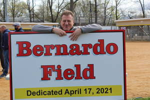 Clark Recreation Director Ralph Bernardo poses with new sign for field named in his honor.