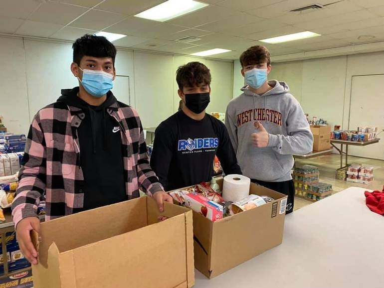 Lucas Regan, Benjamin Root, and Jake Monroy volunteer at the IHM food pantry in Scotch Plains.