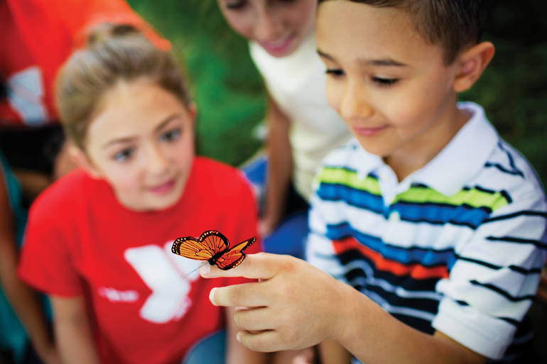 Campers observe a butterfly that landed on a boy's finger.