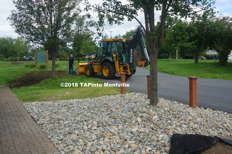a Lars Darling, in the distance, speads soil so that new grass seed can be laid down at the Dog Park ©2018 TAPinto Montville.JPG