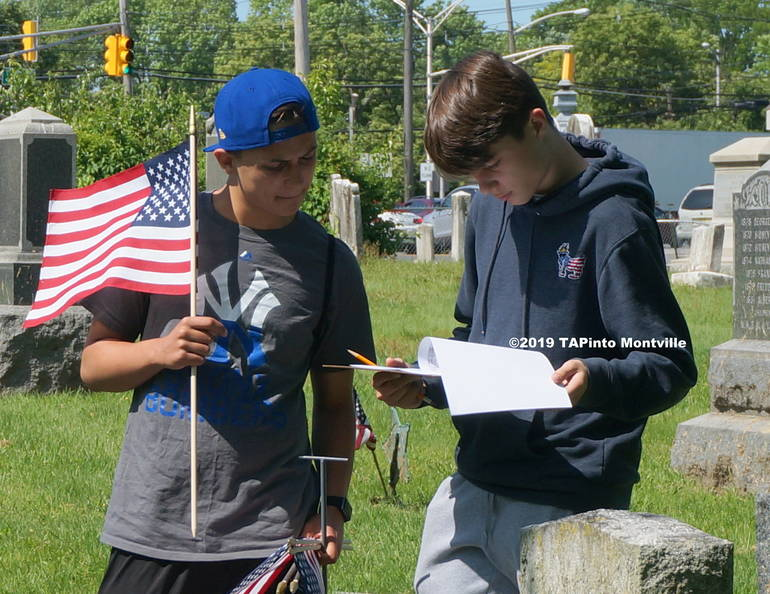 a Lazar students check names on their list as they replace flags at the Pine Brook Cemetery on Hook Mountain Road ©2019 TAPinto Montville   1.JPG