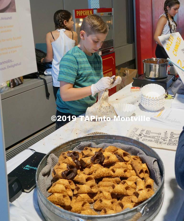a Nolan Shenkman fills a cannolo at Nolie's Cannolis ©2019 TAPinto Montville.JPG