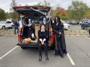 Two people in Adams Family contest near a trunk decorated for Halloween in Berkeley Heights,  NJ.