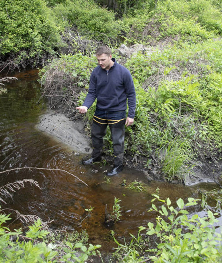 Biologist Mike Rosellini inspects a mosquito breeding ground off a main road in Lincoln Park CROP.jpg