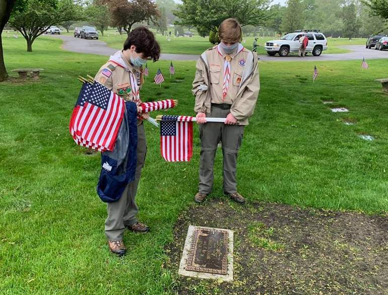 Scouts from Troop 104 in Scotch Plains place flags at the headstones of veterans in observance of Memorial Day.
