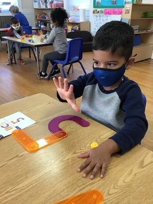 """A young boy wearing a face masks counts """"5"""" on his fingers."""