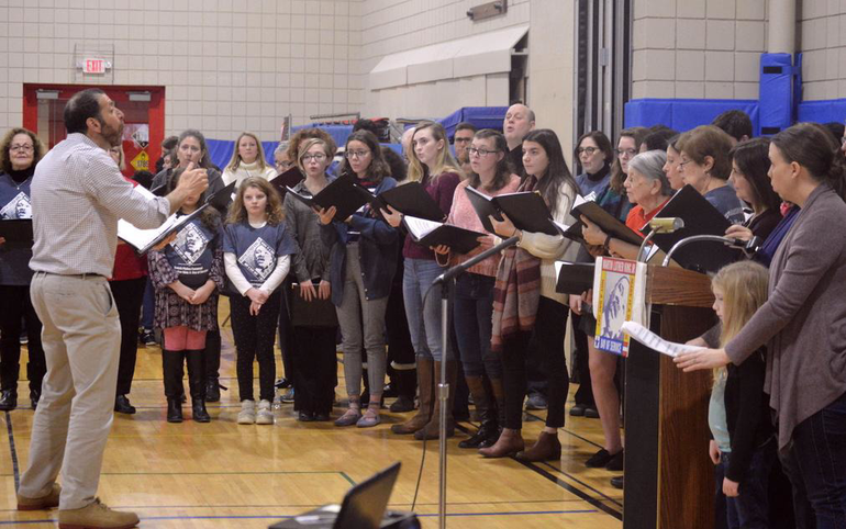 Cantor Matt Axelrod conducts the community choir - wide shot.png