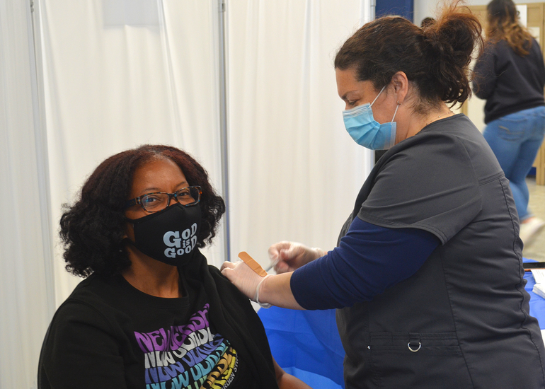Carita Wallace of St. John's Baptist Church in Scotch Plains receives COVID vaccine from Carolyn Sorge.