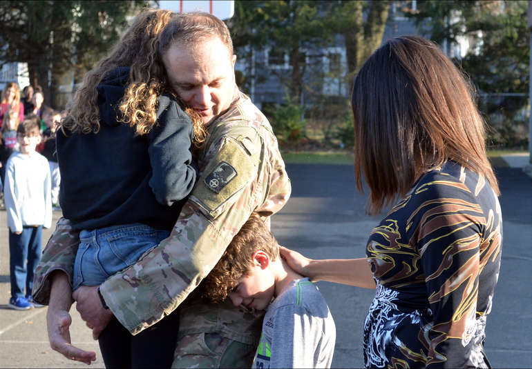 Capt. Moore hugs his daughter, Reland, and son Spencer appreciates his return and mom, Michele, looks on..png