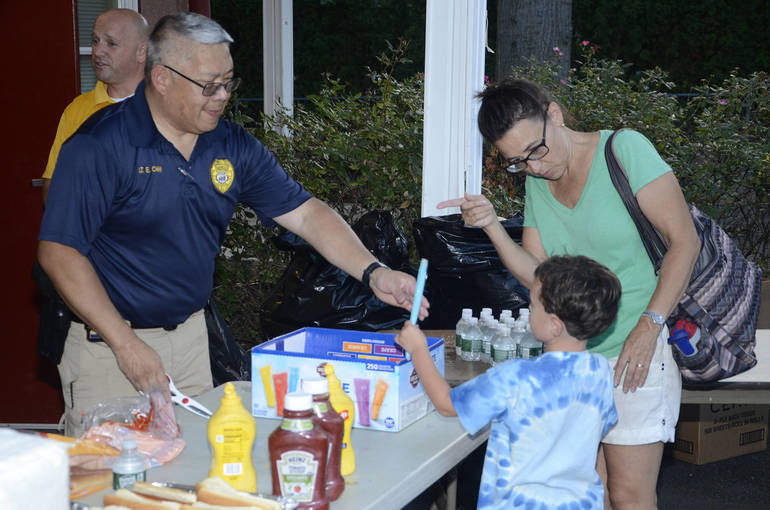 Fanwood police Lt. Gene Chin dispenses ice pops.