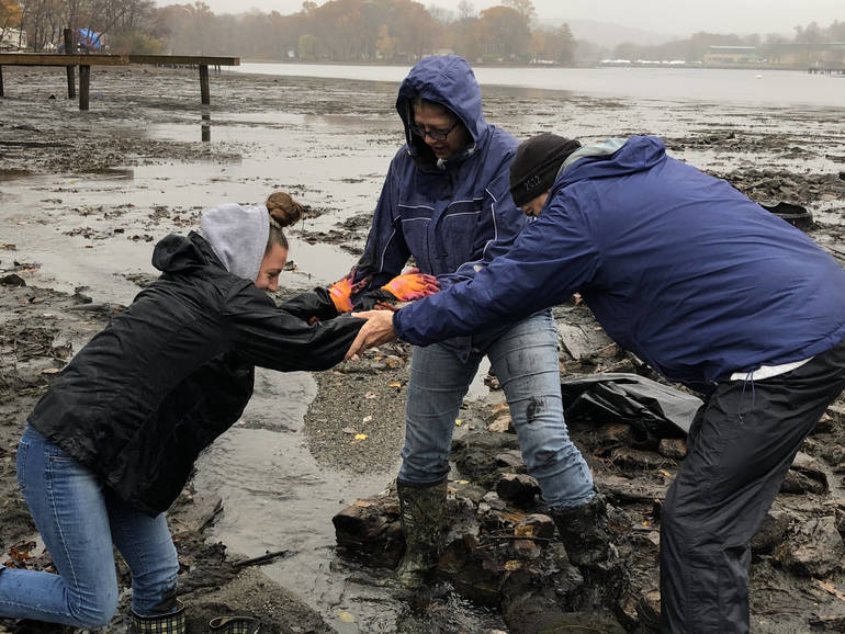 Cora Haughney (left) gets assistance from her mother, Roxana Scanlon (center), and volunteer Bill Woolley (right) when her boots got stuck in the muck during the lake-wide clea.jpg
