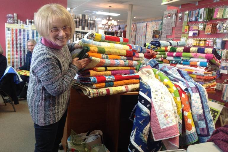 Debbie Greaney with completed quilts