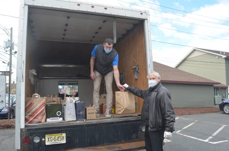 Scotch Plains Mayor Al Smith hands non-perishable foods to Ron Shovlin.