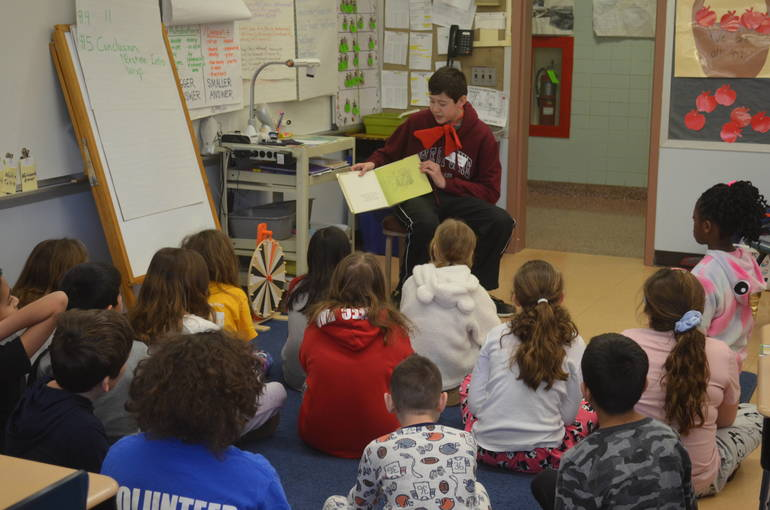Julian Meinke, a student at Terrill Middle School, reads to fourth graders at Coles Elementary School.