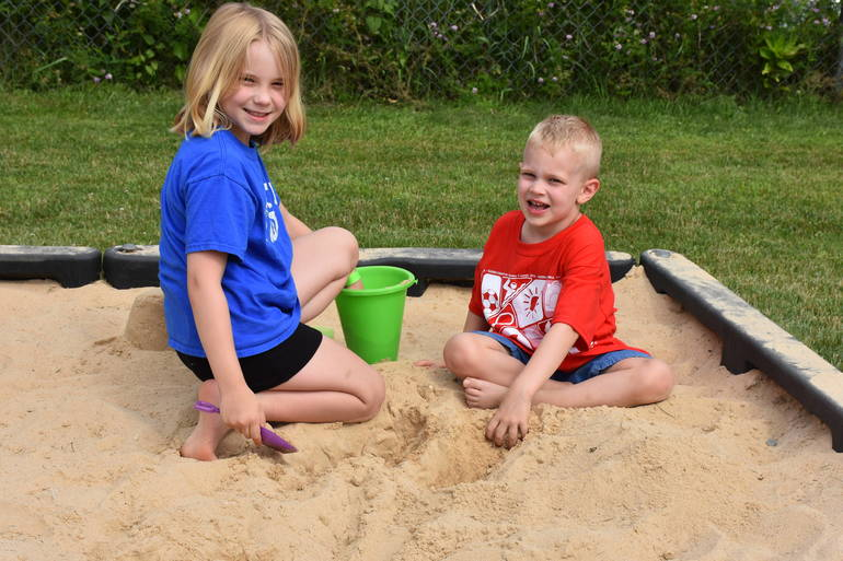 A young girl and boy play in a sandbox.