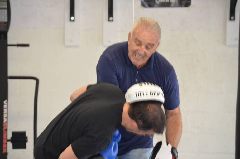 Gerry Cooney clowns around with a participant in his boxing class.