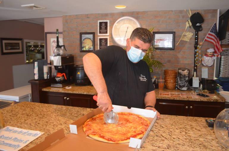 Ronnie Vojka of Fabio's Bistro in Fanwood cuts a pizza.