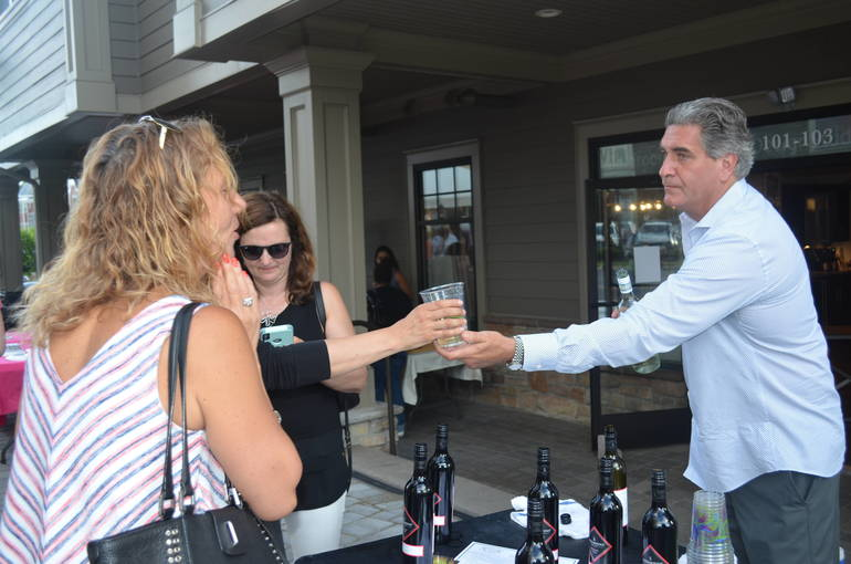 Sean Flannery of Sheelen's Crossing serves wine at Ladies Night Out in downtown Fanwood on Thursday, June 6, 2019.