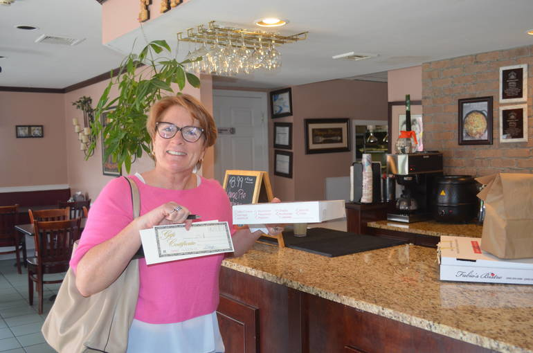Fanwood's Director of Economic Development Liz Jeffery gets takeout and a gift certificate from Fabio's