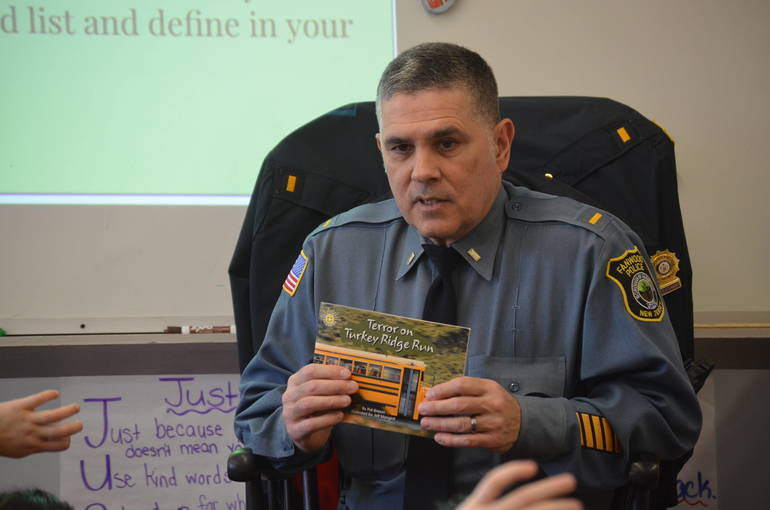 Fanwood police lieutenant Francisco Marrero reads to students at Coles School.