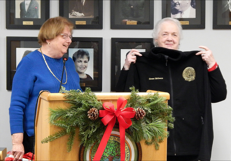 Fanwood Borough Administrator Eleanor McGovern holds up a fleece presented by Councilwoman Kathy Mitchell.