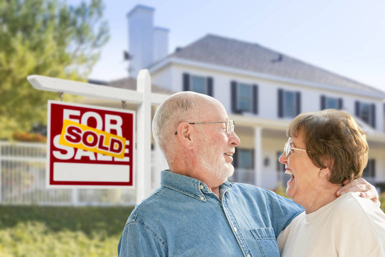 Empty nesters in front of sold sign September 2018 edd.jpg