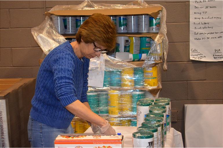 Evangel Church volunteer makes sanitary packs.png