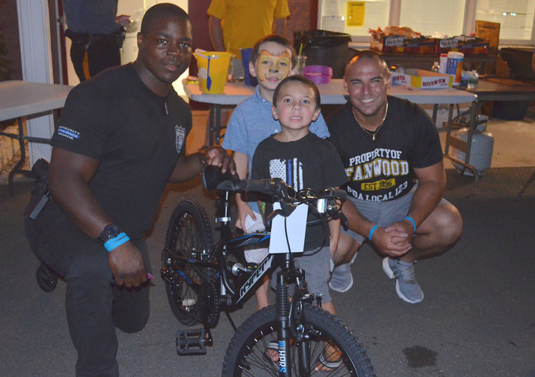 Fanwood police officers Tim Green and Dan Piccola with bicycle prize winners.png