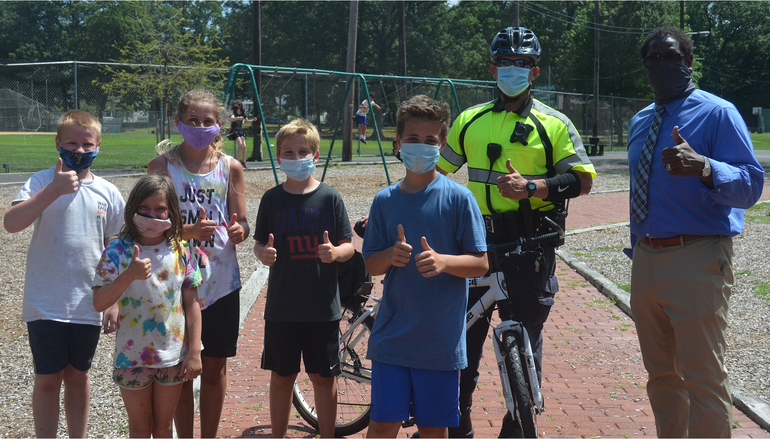 Fanwood Bicycle officer Kevin Stomber and Councilman Anthony Carter with young Fanwood residents.png