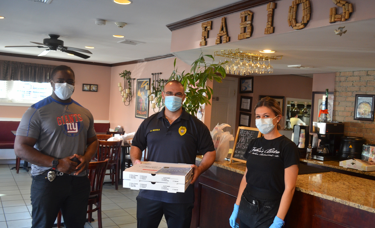 Fanwood Police Officers Tim Green and Dan Piccola pick up pies from Fabio's Bistro for delivery to contest winners..png