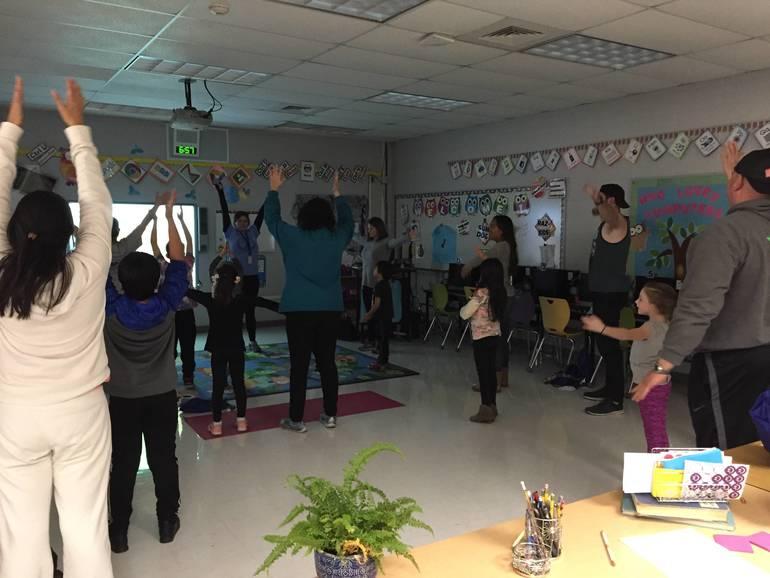 Families practice yoga poses.JPG