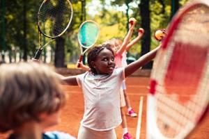 Diverse group of children practicing tennis skills.