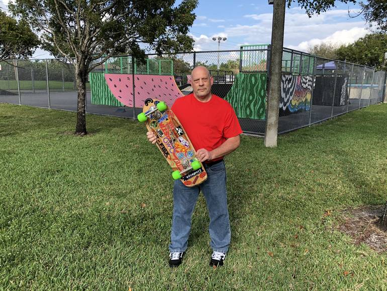 Steve Simmons holding one of his skateboards next to the skateboarding facility at Betti Stradling Park in Coral Springs.