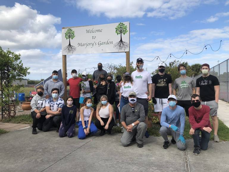 Students, staff and Tunie's Market managers gathered Saturday at Marjory's Garden to harvest vegetables, pick flowers, and clear weeds.