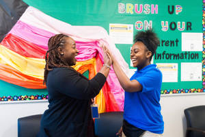 Camden student and teacher high five in the classroom.