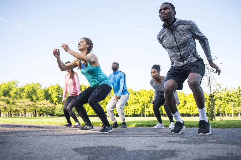 Diverse group of adults perform fitness routine.