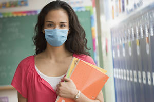 Female teacher with long hair wearing a face mask and carrying notebooks.