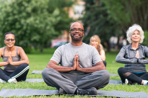 A diverse group of adults perform a yoga routine.