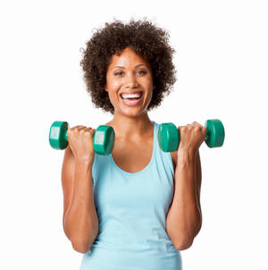 A woman holding weights and smiling.