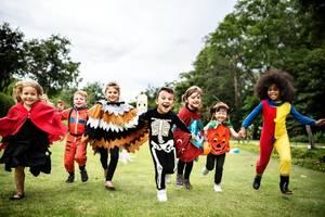 Children in costume running on grass.