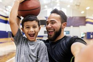 A father and son smile while holding a basketball.