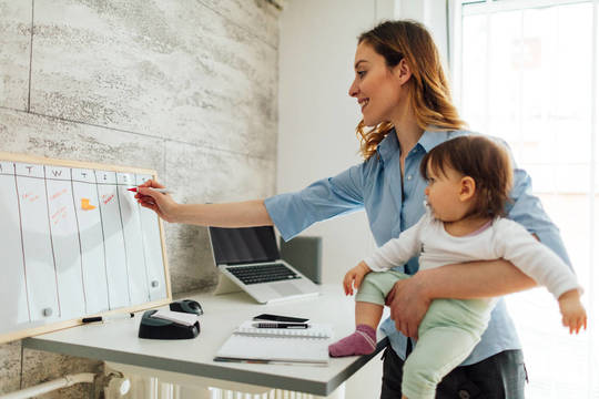 Top story 17d195941fe56bca3eab istock mother working from home   baby   calendar size medium