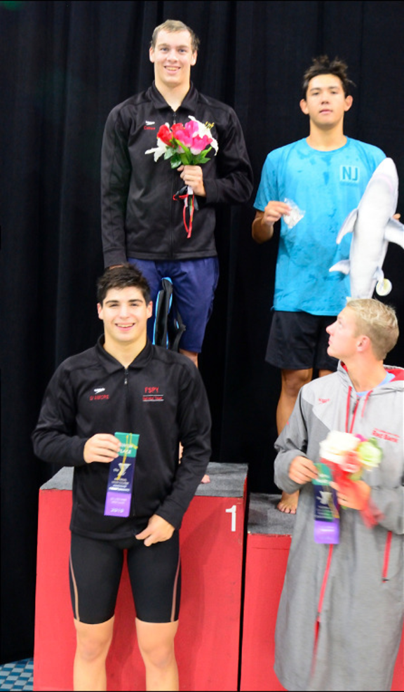 Josh Cohen on podium with Logan.png