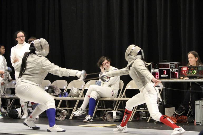 Junior saber Cierra Blair (left, blue sock) gets a point on Super Saturday.jpg