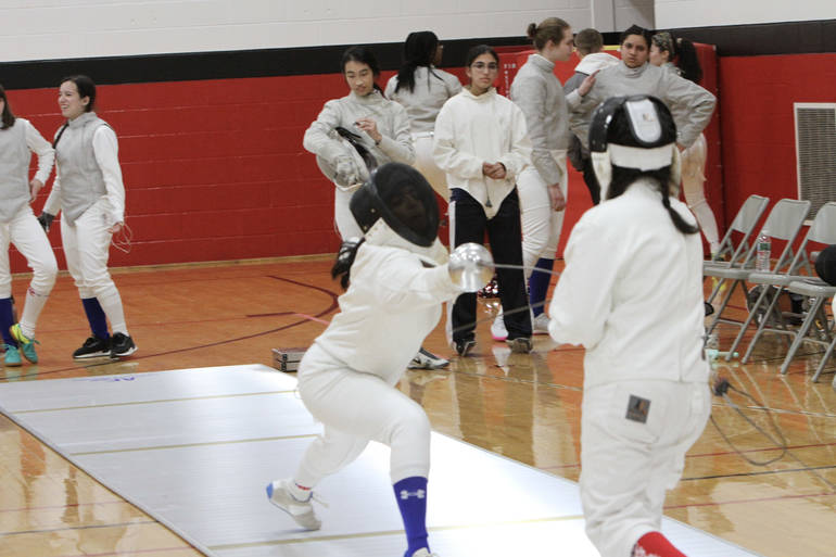 Junior epee Ritika Sinha-Chaudhuri extends during a winning bout at West Essex.jpg