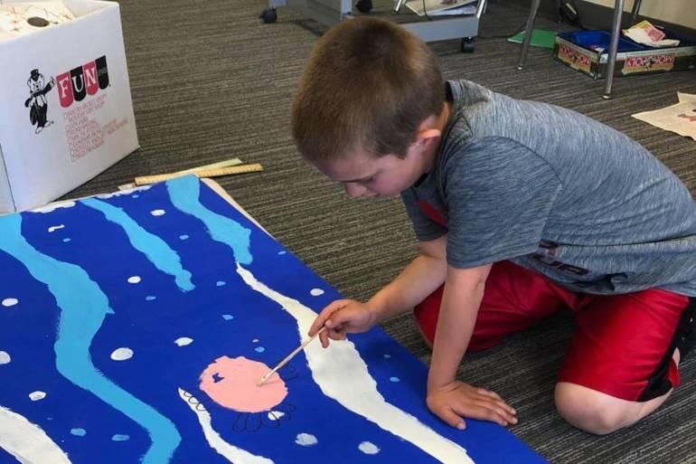 Kennedy boy painting mural board.jpeg