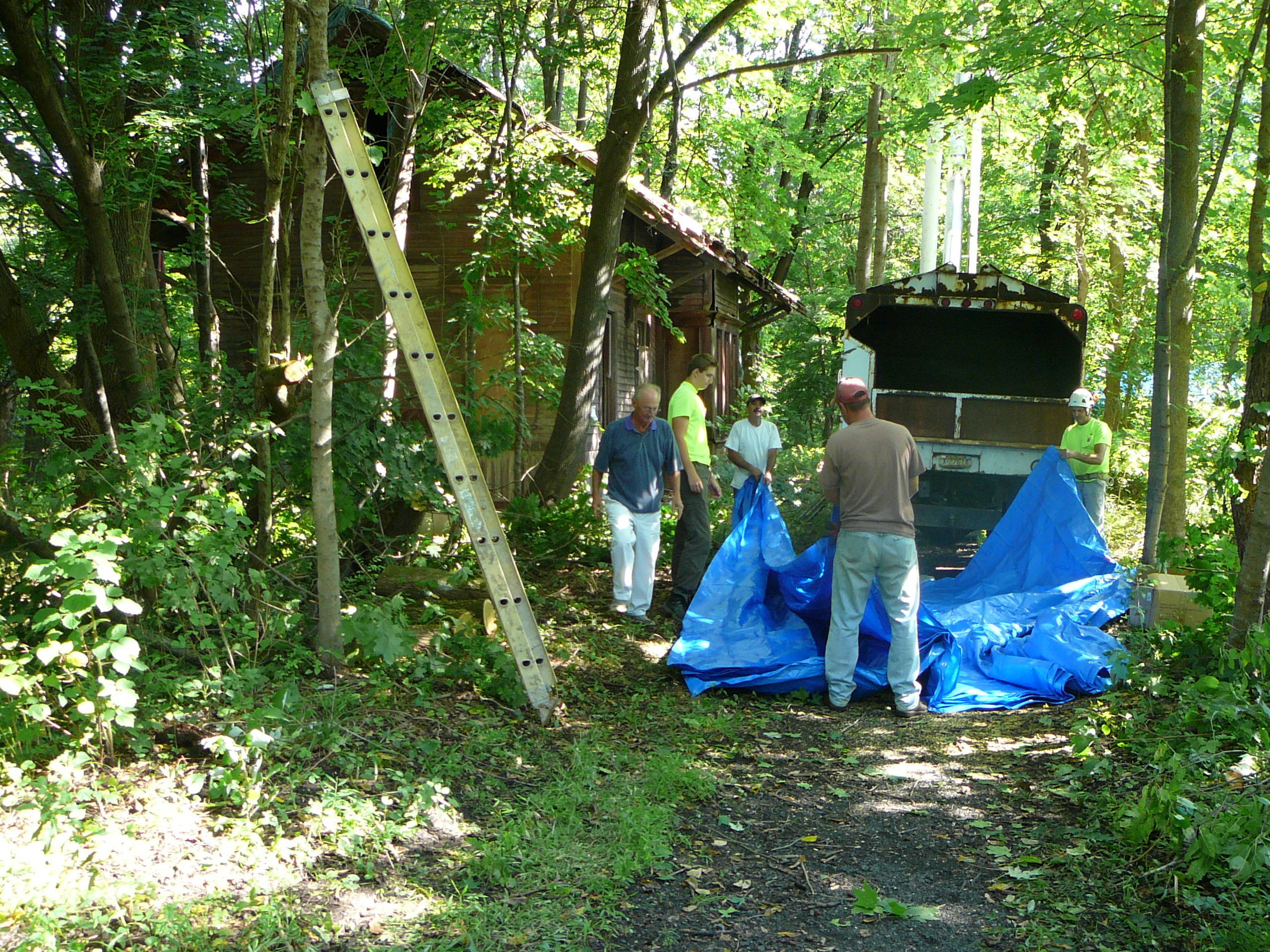 Men from Spanner Tree & Shrub Care of Pittstown and Merco, Inc. of Lebanon work on covering the historic train station in Pittstown with two large tarps..JPG