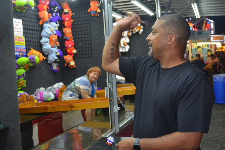 Councilman Roc White plays a dart game at the St. Bart's Italian Festival in Scotch Plains on Labor Day