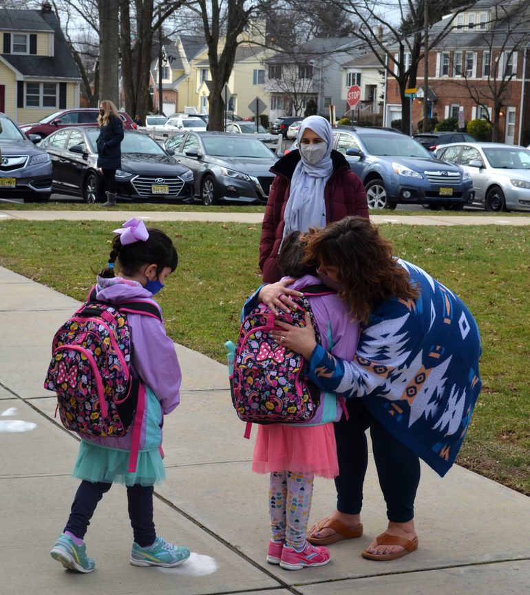 A mom hugs her daughters after the first day of school at Evergreen Elementary in Scotch Plains.