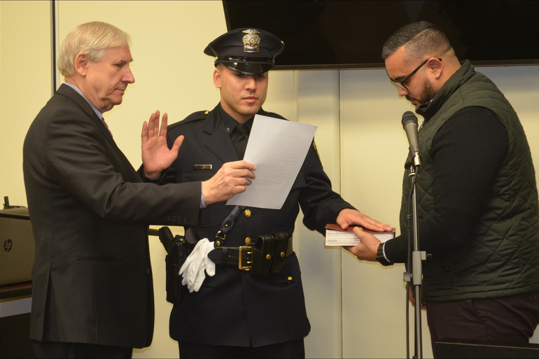 Scotch Plains police officer Javier Maldonado takes oath as his brother holds the Bible.